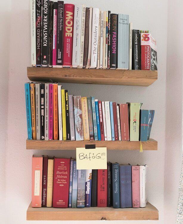Blick auf ein Bücherregal, daran klebt ein Zettel mit der Aufschrift