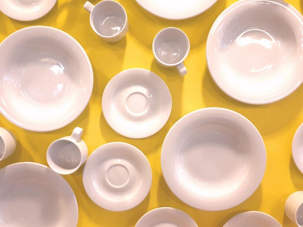 Weiße teller und Tassen auf gelbem Untergrund