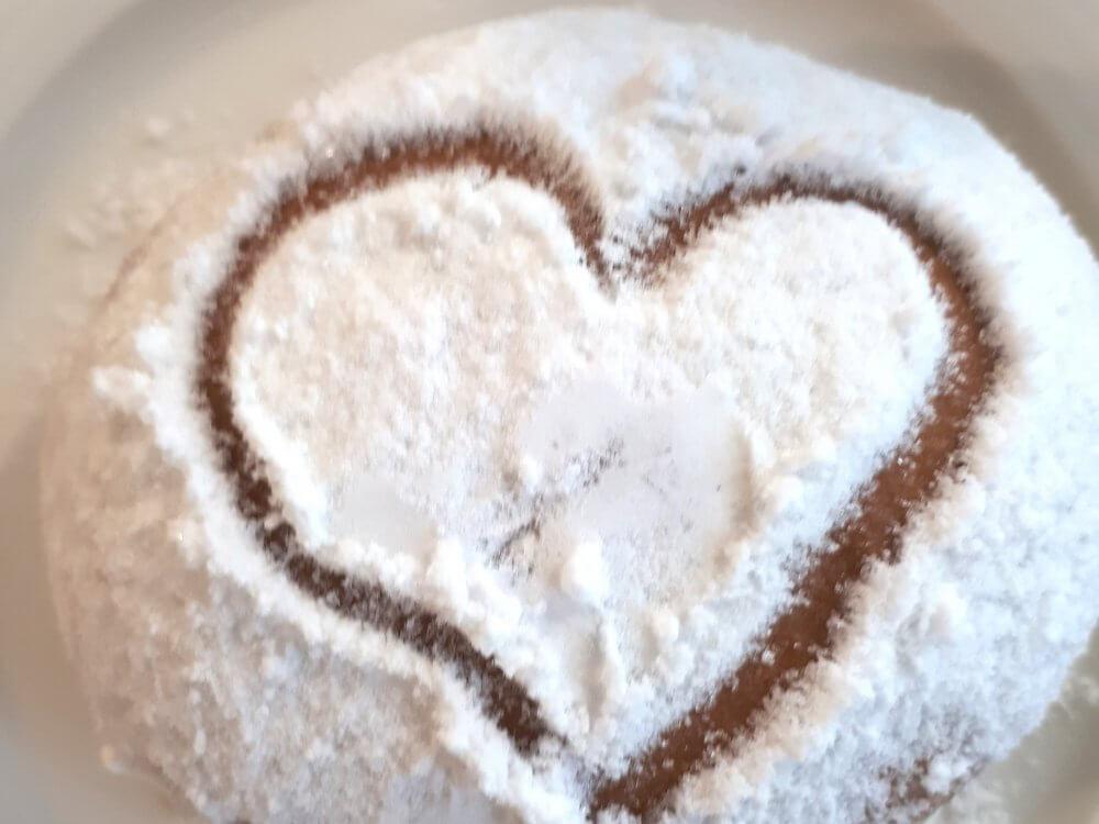 Blick auf einen Berliner, in dessen Zuckergarnitur ein Herz eingemalt ist