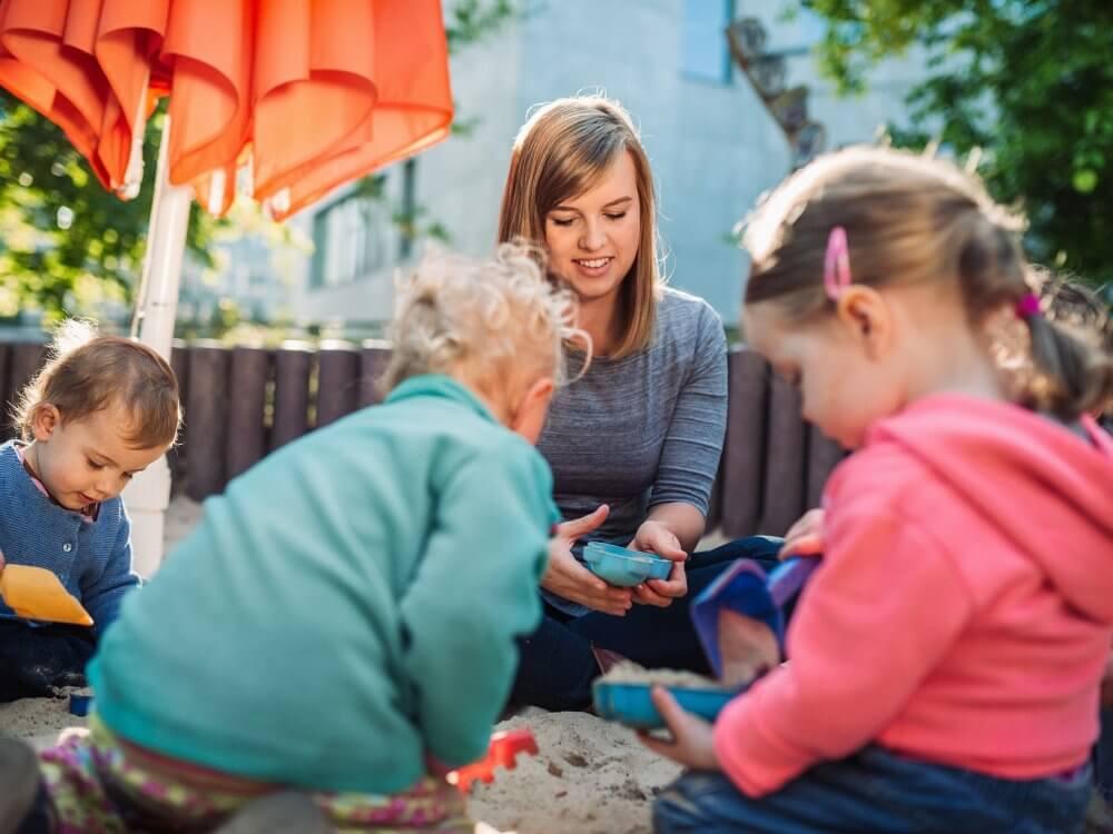 Eine junge Frau und zwei Kinder spielen draußen