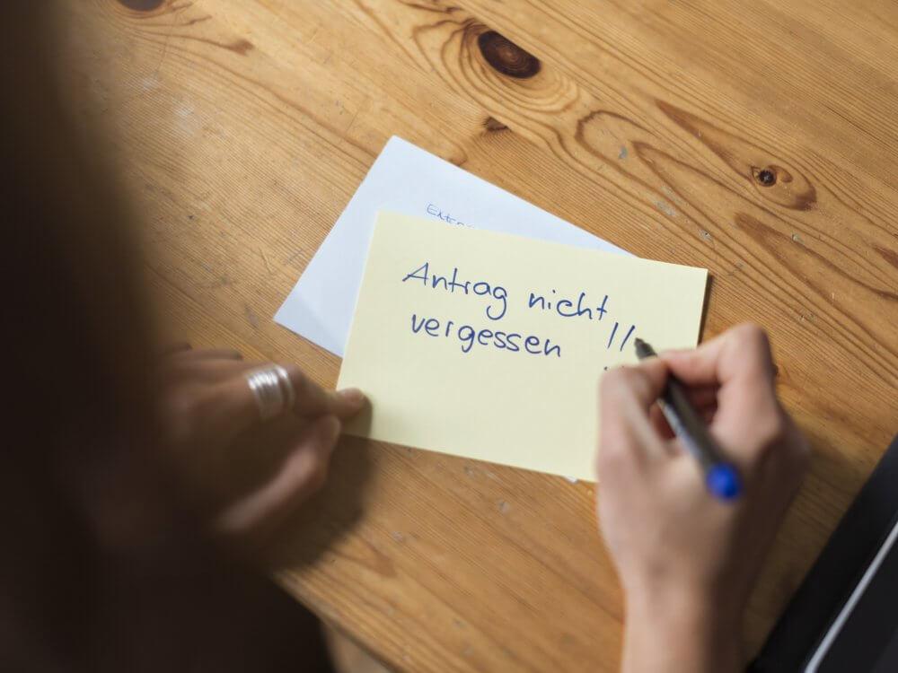 Frauenhände machen eine Notiz auf einem Zettel, darauf steht: