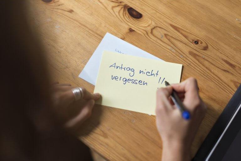 """Frauenhände machen eine Notiz auf einem Zettel, darauf steht: """"Antrag nicht vergessen"""""""