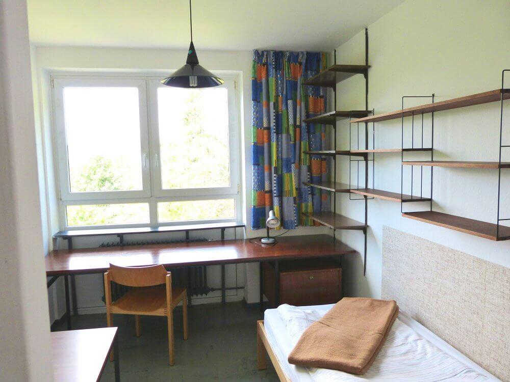 Ein klassisches Einzelzimmer mit Bett, Regal, Schreibtisch und Stuhl