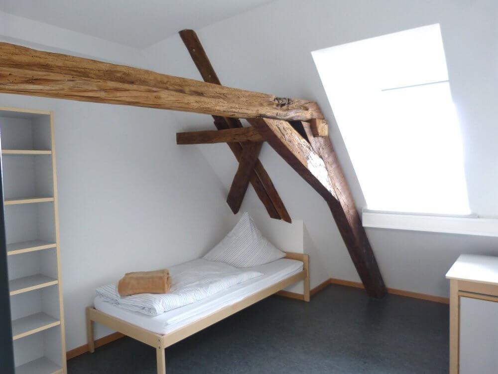 Zimmer unterm Dach in der Ritterstraße - ein deckenbalken ist freigelegt, darunter steht das Bett