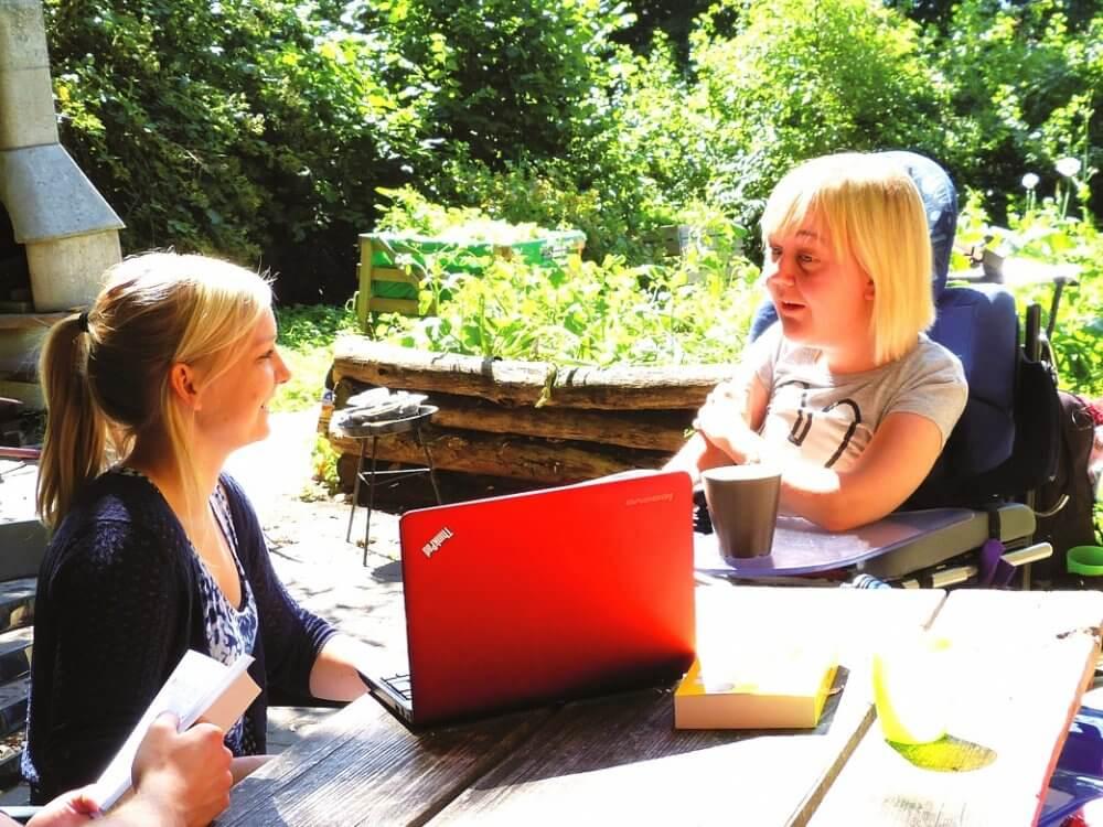 zwei junge Frauen sitzen am Tisch i Garten vor einem Laptop, eine Frau nutzt einen Rollstuhl