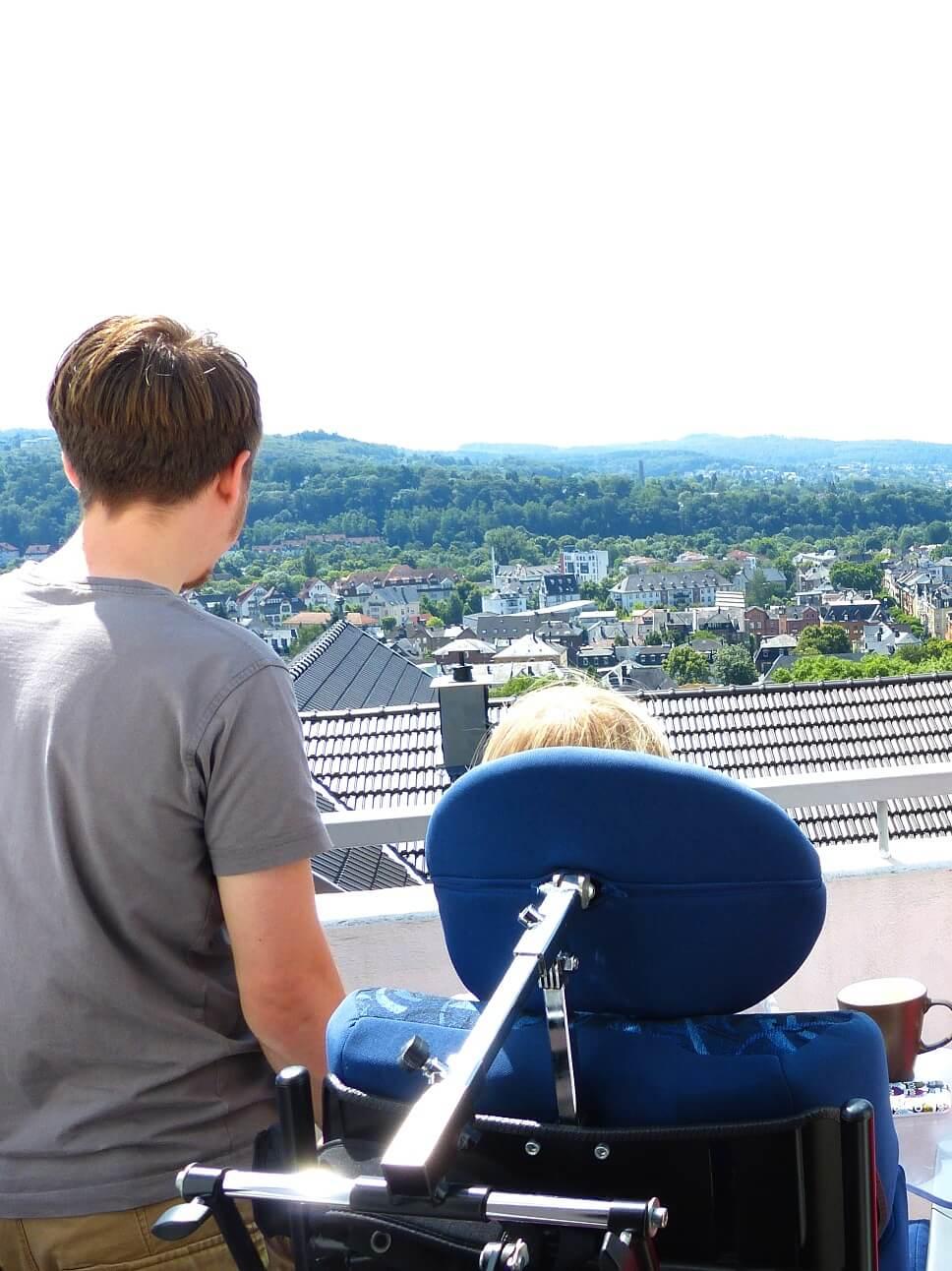Ein junger Mann steht neben einer jungen Frau, die im Rollstuhl sitzt