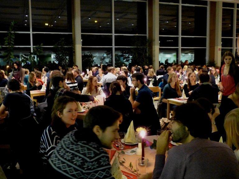 Studierende sitzen im Speisesaal, der mit kerzenschein beleuchtet ist