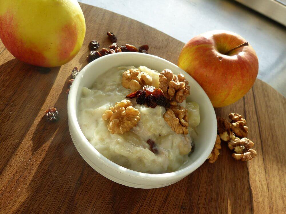 Ein Dessertschälchen, daneben Nüssen und Äpfel