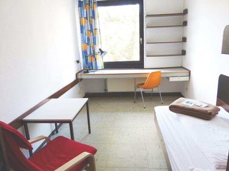 Blick in ein klassisches Einzelzimemr mit Bett, Schreibtisch und Sessel