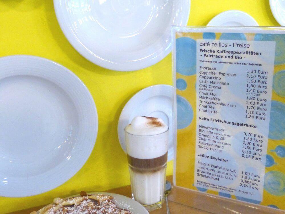 Blick auf einen Kaffee im Glas vor der Wand des cafe zeitlos