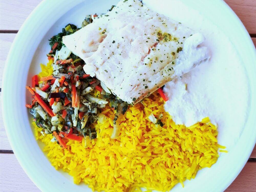 Reis, Fisch und gemüse auf einem weißen Teller