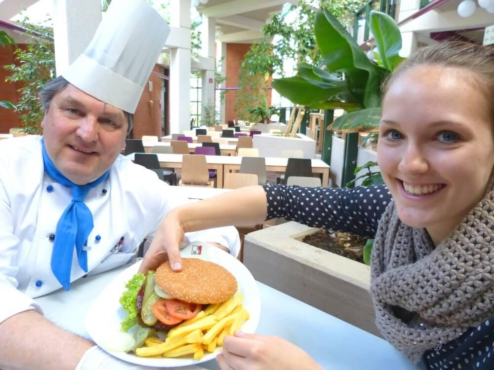 Ein Koch bietet einer jungen Frau einen Hamburger an