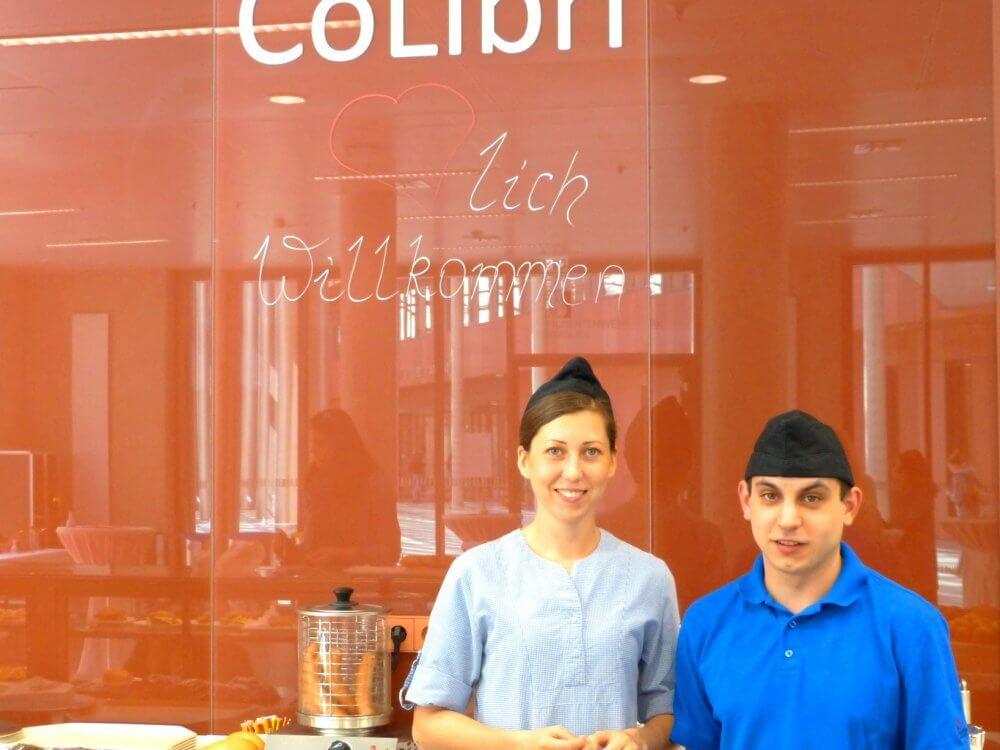 Zwei Mitarbeiter des Cafés Colibri vor einer roten Wand