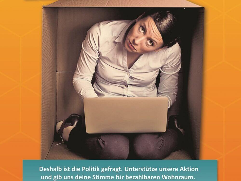 Eine Frau sitzt im Pappkarton mit einem Laptop auf dem Schoss