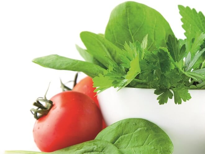 Krüter, eine Tomate und Salat in einem weißen Schälchen