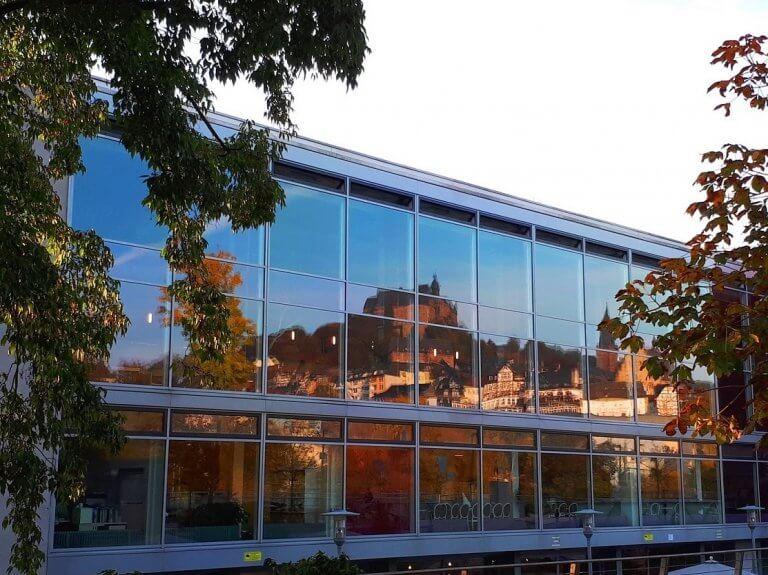 Außenansicht der mensa erlenring - im Fenster spiegelt sich das Panorama der Stadt