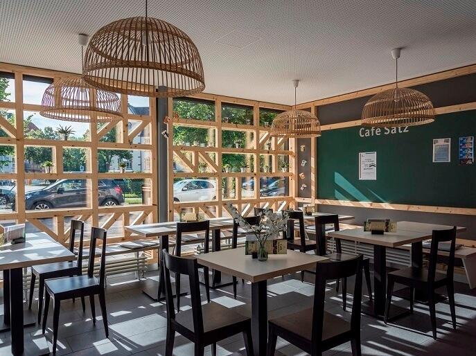 Tische und Stühle des gemütlochen kleinen Café Satz im Wohnheim Gutenbergstraße