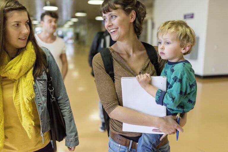 Studentin mit Kind auf dem Arm