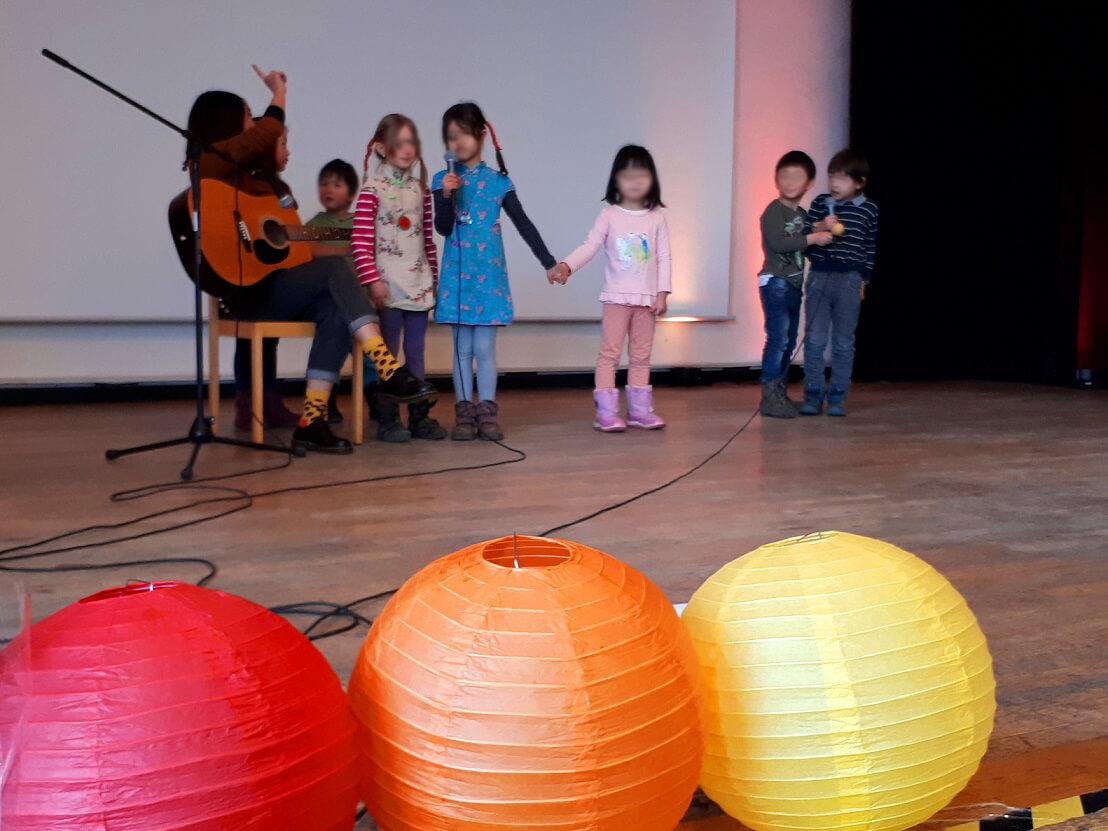 Kinder stehen singend auf der Bühne