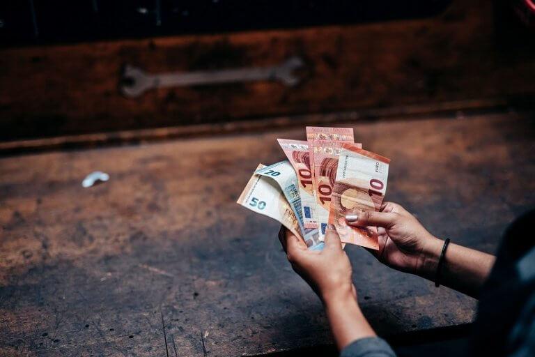 zwei Hände halten Geldscheine fest