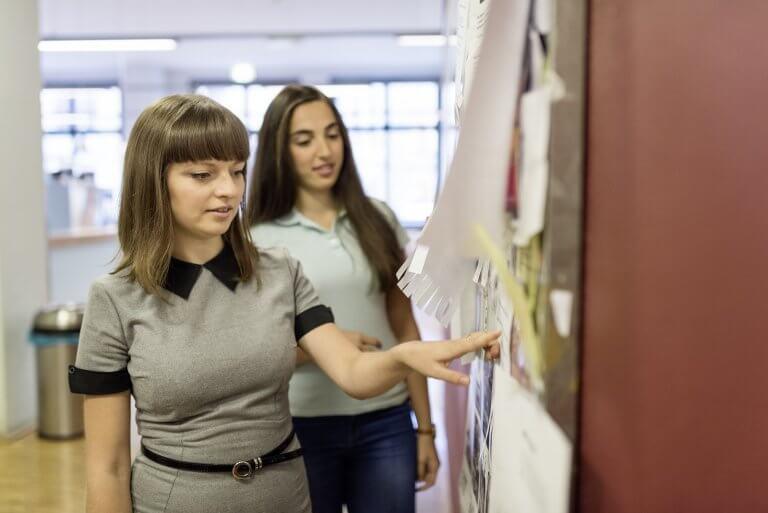 zwei Studierende lesen Aushängean einem schwarzen Brett